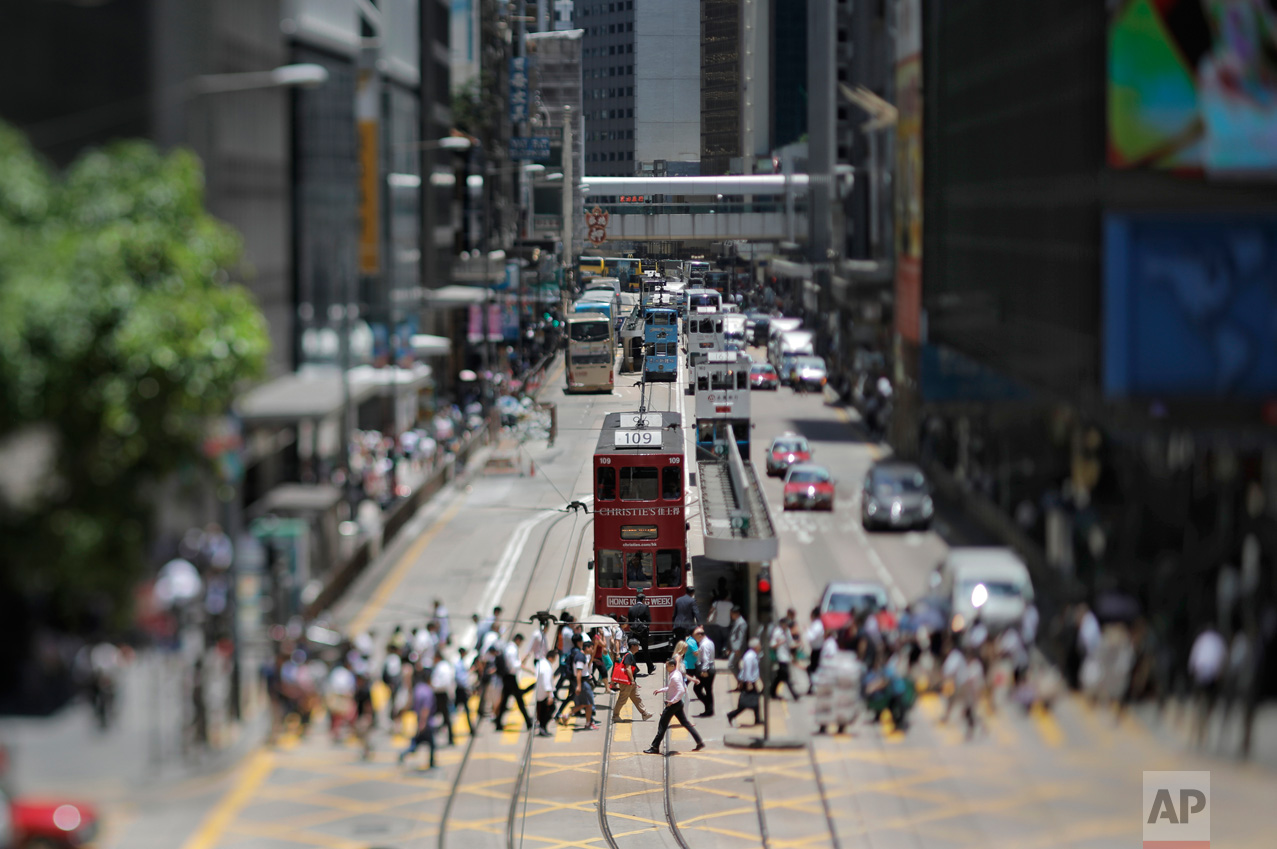In this May 31, 2017, photo made with a tilt-shift lens, people walk at Central district in Hong Kong. Two decades since Beijing took control of Hong Kong, China's rising influence – and Britain's waning profile – are impossible to ignore. (AP Photo/Vincent Yu)