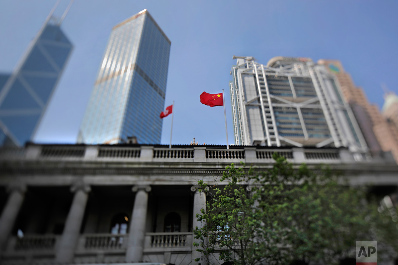 In this May 29, 2017, photo made with a tilt-shift lens, a Chinese national flag and a Hong Kong flag fly above the Court of Final Appeal in Hong Kong.(AP Photo/Vincent Yu)