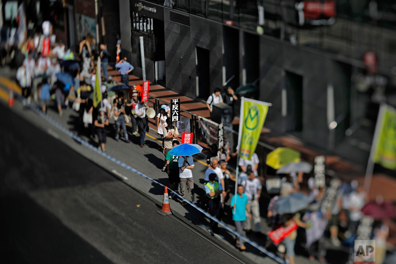 """In this May 28, 2017, photo made with a tilt-shift lens, protesters in Hong Kong carry placards with Chinese words that read: """"Exonerate the June 4 Protest"""" as hundreds of Hong Kong people march on a downtown street to mark the 28th anniversary of China's crackdown on Tiananmen Square. Two decades since Beijing took control of Hong Kong, China's rising influence – and Britain's waning profile – are impossible to ignore. (AP Photo/Vincent Yu)"""