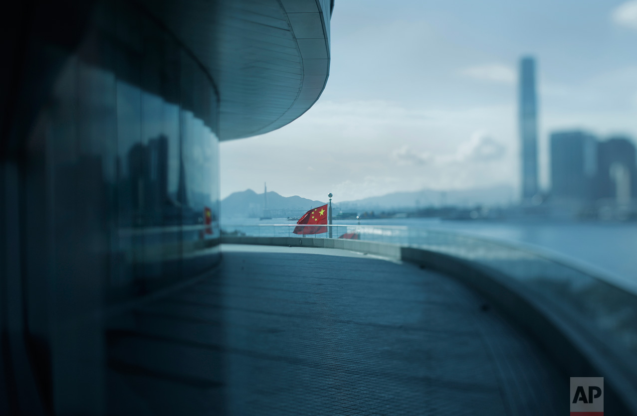 In this June 7, 2017, photo made with a tilt-shift lens, a Chinese national flag flies at the Convention and Exhibition Center in Hong Kong. Hong Kong's massive waterfront convention center was the venue for 1997's handover ceremonies, where Chinese and Beijing officials presided over the transfer of power beginning at midnight on June 30, 1997. It will be a key location for the 20th anniversary events attended by President Xi Jingping. (AP Photo/Vincent Yu)