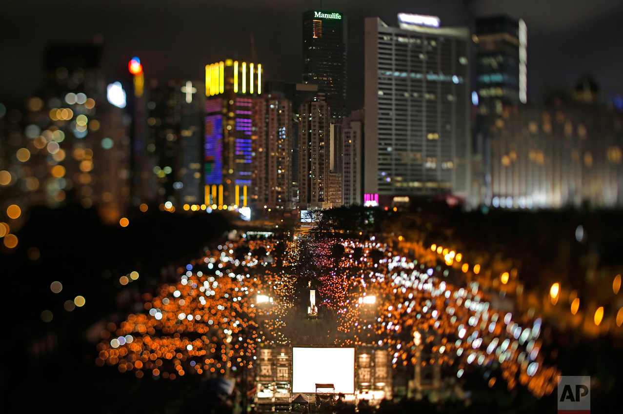 In this June 4, 2017, photo made with a tilt-shift lens, tens of thousands of people attend a candlelight vigil in Victoria Park in Hong Kong for victims of the Chinese government's military crackdown nearly three decades ago on protesters in Beijing's Tiananmen Square. Two decades since Beijing took control of Hong Kong, China's rising influence – and Britain's waning profile – are impossible to ignore. (AP Photo/Vincent Yu)