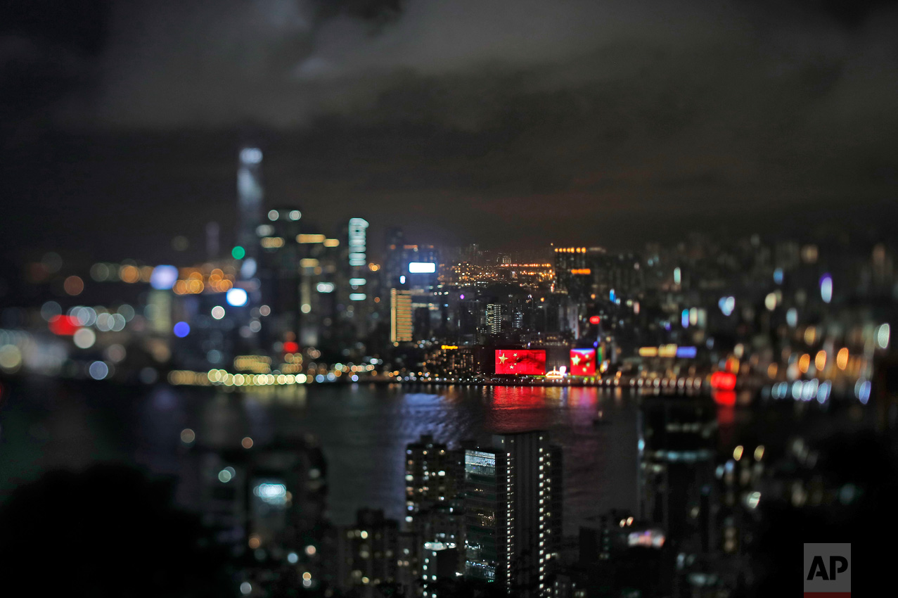 In this June 24, 2017, photo made with a tilt-shift lens, a Chinese national flag appears on a screen to mark the 20th handover anniversary at Victoria Habor in Hong Kong. Hong Kong's famous waterfront retains its British colonial era name and was the scene of Britain's farewell from its colony. Since Beijing took control of Hong Kong in 1997, China's rising influence – and Britain's waning profile – are impossible to ignore. (AP Photo/Vincent Yu)