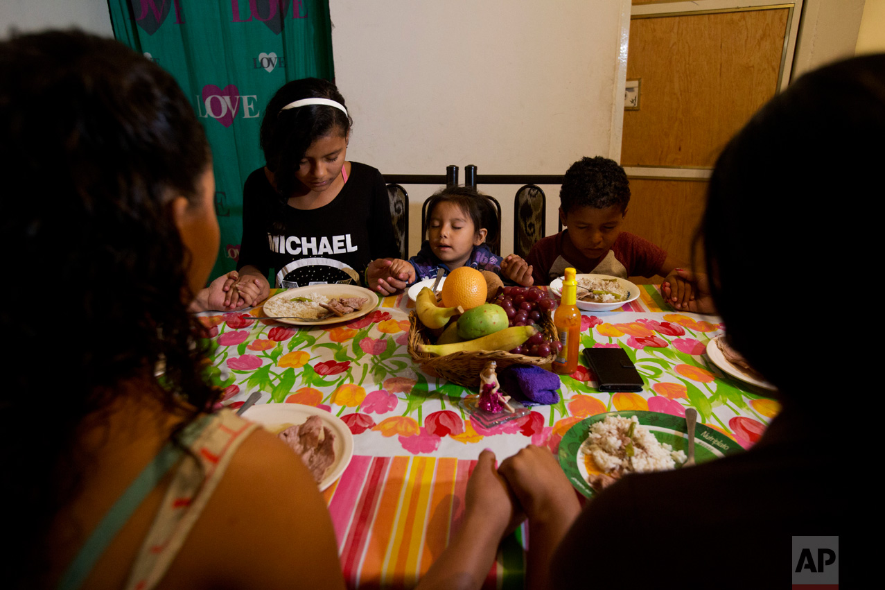 In this June 27, 2017 photo, three-year-old Carlita Perez, center, from El Salvador, says grace along with, from left, Honduran siblings Laura, Ruth, and Josue Funez Cruz, and their cousin Emma Karina Cruz, as they sit down to dinner in the two-bedroom apartment the two families share in the Iztapalapa district of Mexico City. (AP Photo/Rebecca Blackwell)