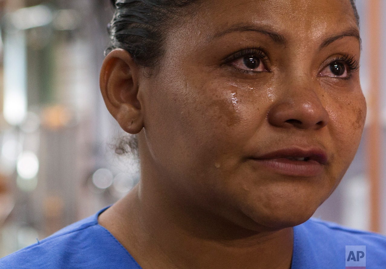 In this June 27, 2017 photo, Laura Maria Cruz Martinez of Honduras cries as she recounts the fear she felt for her children when she, another fellow single mother and the nine kids in their care fled their homes only hours after receiving gang threats, during an interview at the medical supplies store where she now works in the Doctores neighborhood of Mexico City. (AP Photo/Rebecca Blackwell)