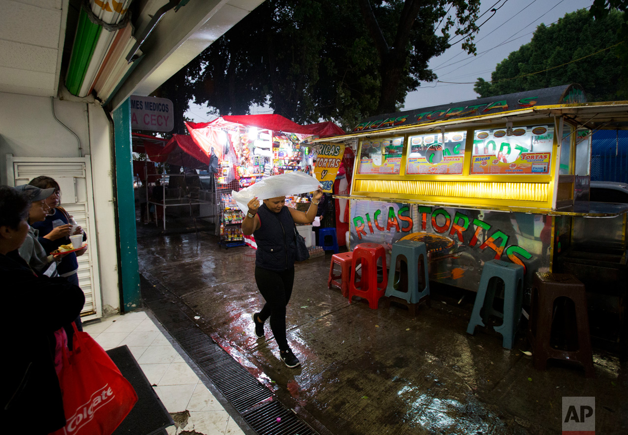 In this June 27, 2017 photo, Honduran refugee Laura Maria Cruz Martinez shields herself from a rainy season downpour with a thin plastic poncho as she walks from the medical supply store where she works to the nearest subway station, in the Doctores neighborhood of Mexico City. (AP Photo/Rebecca Blackwell)