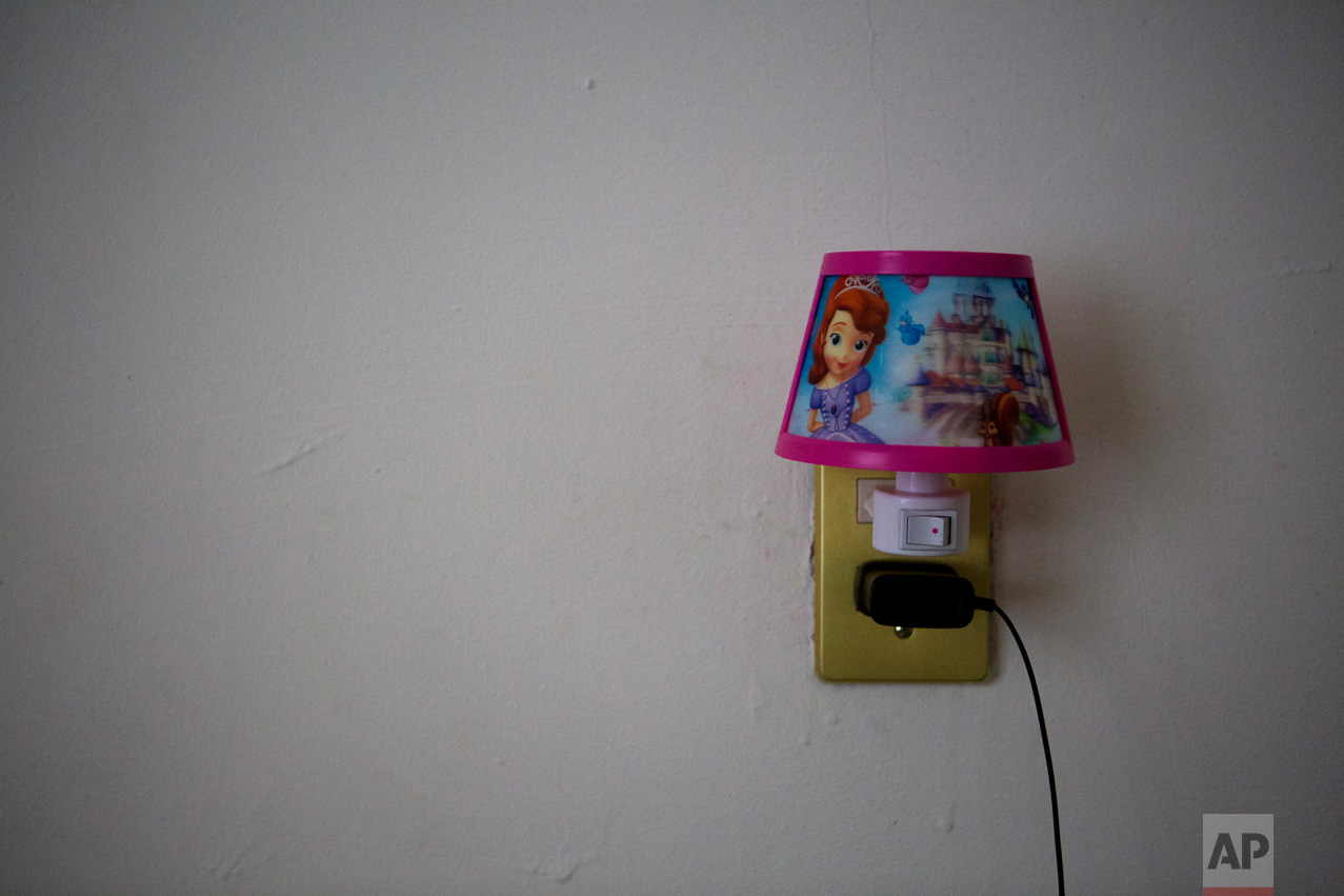 "In this June 22, 2017 photo, a nightlight with images from Disney's ""Frozen,"" is plugged into a socket in the bedroom of Carlita Perez, 3, from El Salvador, and her mother in the two-bedroom apartment they share with Laura Maria Cruz Martinez of Honduras and her family, in the Iztapalapa district of Mexico City. (AP Photo/Rebecca Blackwell)"
