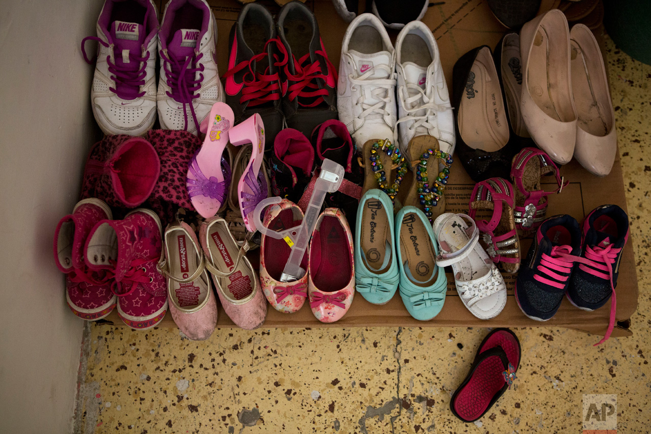 In this June 22, 2017 photo, donated shoes are laid out on cardboard in the bedroom of El Salvadoran refugees Carlita Perez, 3, and her mother in the two-bedroom apartment they share with Laura Maria Cruz Martinez of Honduras and her family, in the Iztapalapa district of Mexico City. (AP Photo/Rebecca Blackwell)