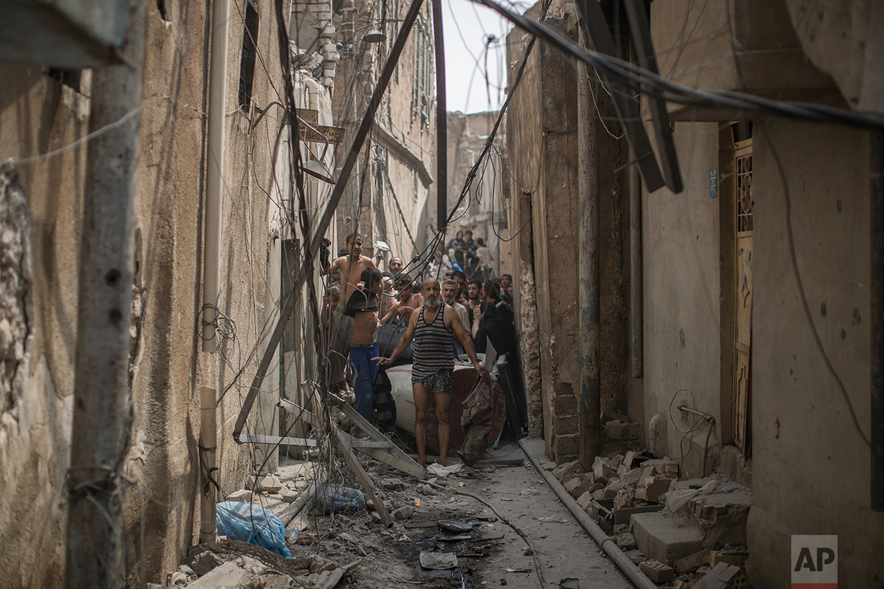Civilians trying to flee get undressed to be checked for explosives after suicide bombers exploded as Iraqi forces continue their advance against Islamic State militants in the Old City of Mosul, Iraq, Monday, July 3, 2017. (AP Photo/Felipe Dana)