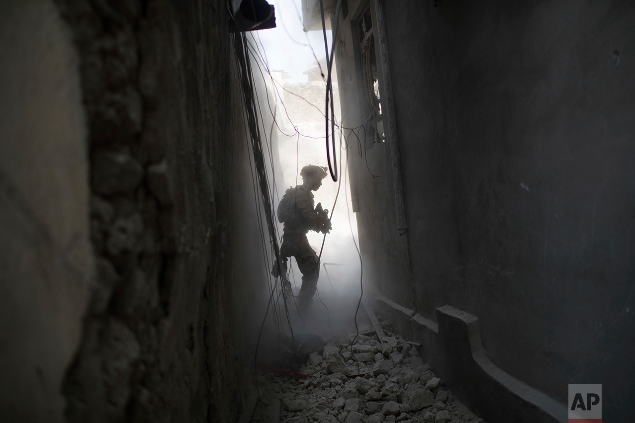 An Iraqi Special Forces soldier exchanges fire with Islamic State militants in the Old City of Mosul, Iraq, Friday, June 30, 2017. (AP Photo/Felipe Dana)