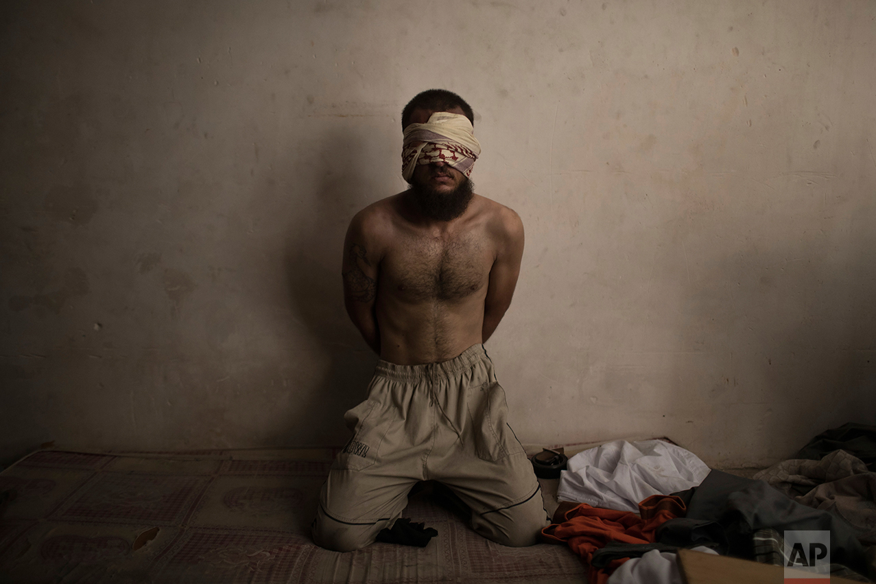 A suspected Islamic State fighter sits in a basement as Iraqi forces continue their advance against Islamic State militants in the Old City of Mosul, Iraq, Monday, July 3, 2017. (AP Photo/Felipe Dana)