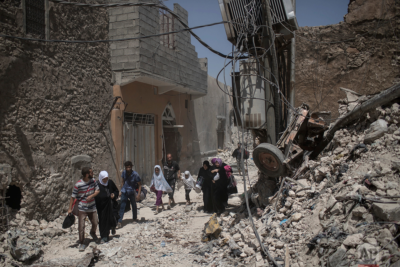 Iraqi civilians flee as Iraqi Special Forces move toward Islamic State militant positions in the Old City of Mosul, Iraq, Thursday, June 29, 2017. (AP Photo/Felipe Dana)