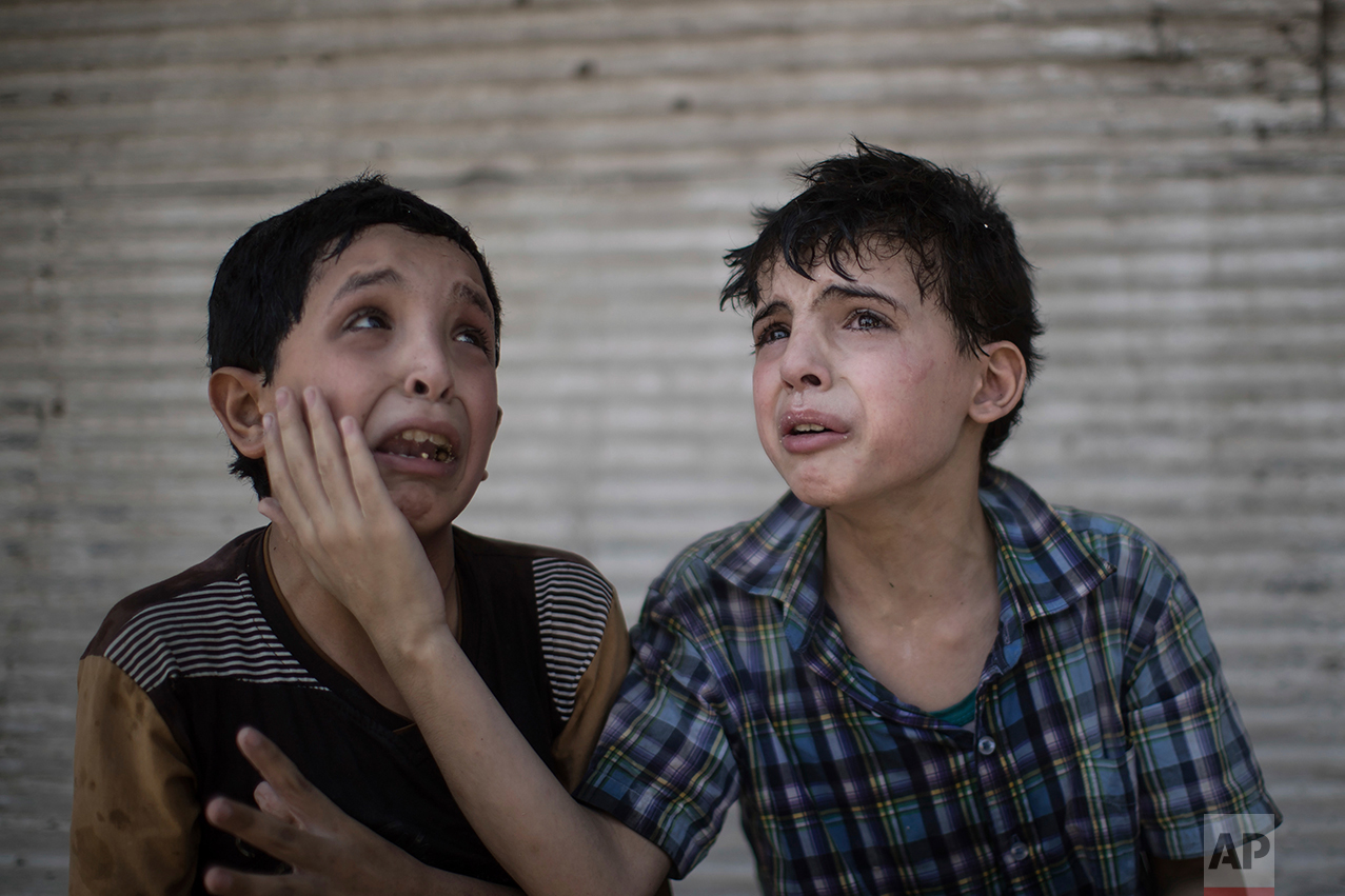 Zeid Ali, 12, left, and Hodayfa Ali, 11, comfort each other after their house was hit and collapsed during fighting between Iraqi forces and Islamic State militants in Mosul, Iraq, Saturday, June 24, 2017. They said some of their family members are still under the rubble. (AP Photo/Felipe Dana)