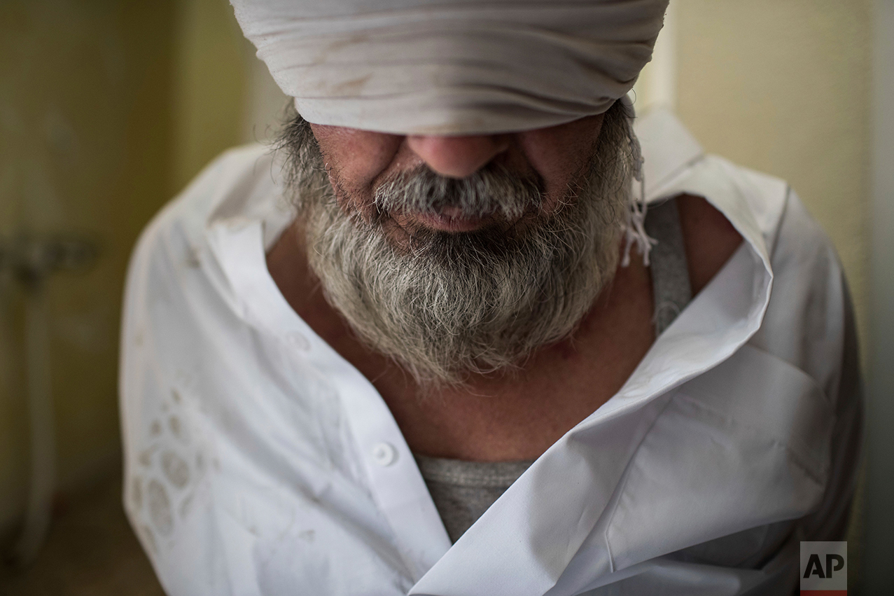 A man suspected to be an Islamic State fighter sits after being detained by Iraqi special forces during conflicts near the old city of Mosul, Iraq, Saturday, June 24, 2017. (AP Photo/Felipe Dana)