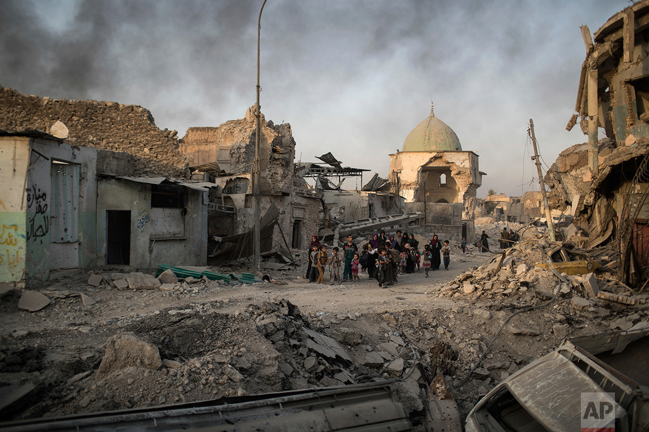 Fleeing Iraqi civilians walk past the heavily damaged al-Nuri mosque as smoke rises in the background in the Old City of Mosul, Iraq, Tuesday, July 4, 2017. As Iraqi forces continued to advance on the last few hundred square kilometers of Mosul held by the Islamic State group, the country's Prime Minister said Tuesday the gains show Iraqis reject terrorism. (AP Photo/Felipe Dana)