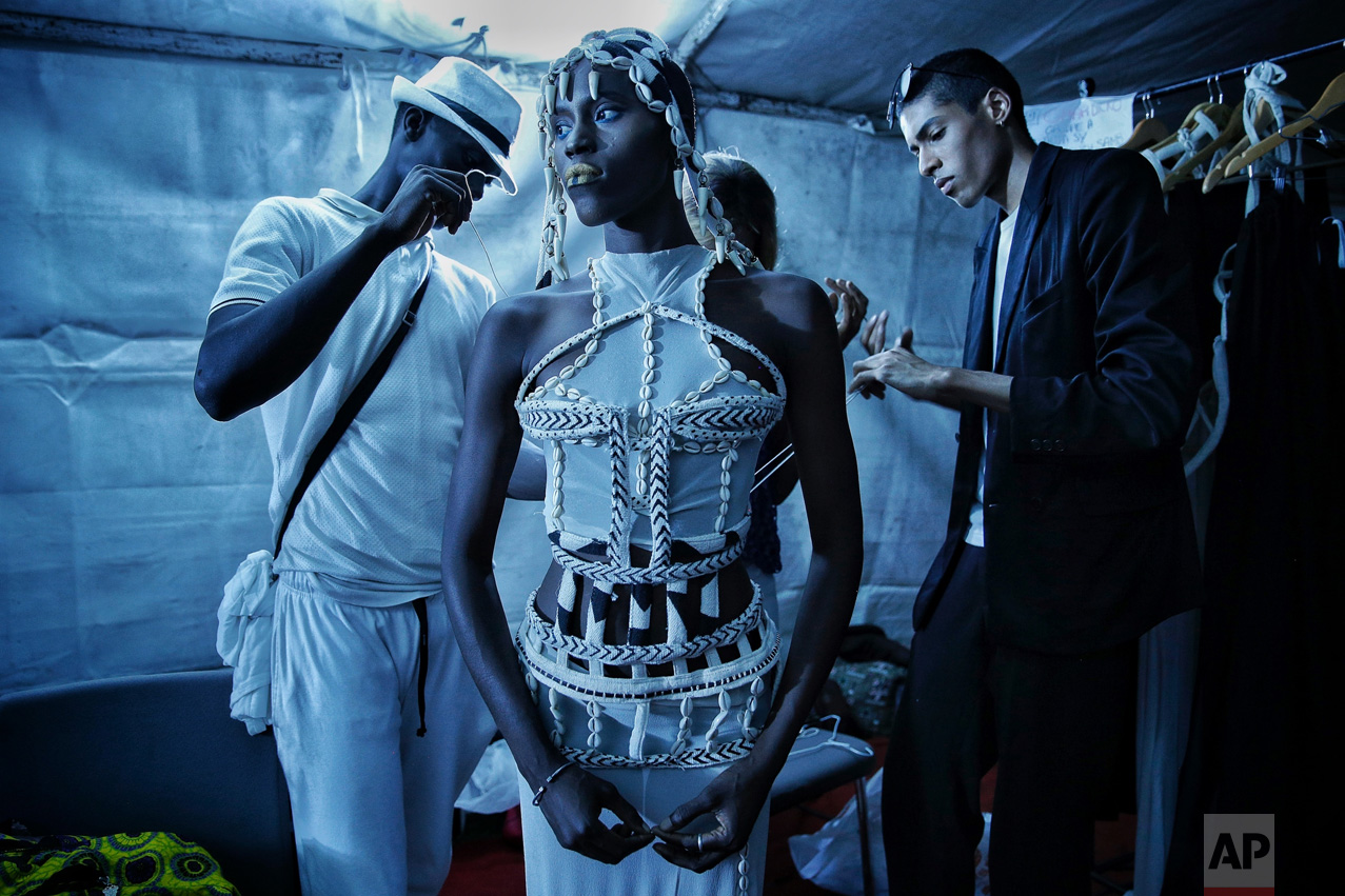 Designer Oumar Dicko, right, of Mali and Belgium, laces up a model in one of his creations backstage during Dakar Fashion Week in the Senegalese capital, Saturday July 1, 2017. (AP Photo/Finbarr O'Reilly)