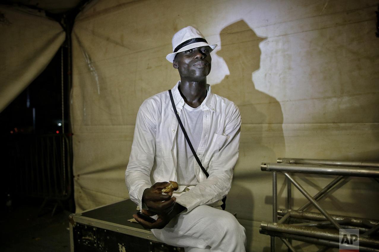 A models eats a sandwich backstage during Dakar Fashion Week in the Senegalese capital, Friday June 30, 2017. (AP Photo/Finbarr O'Reilly)
