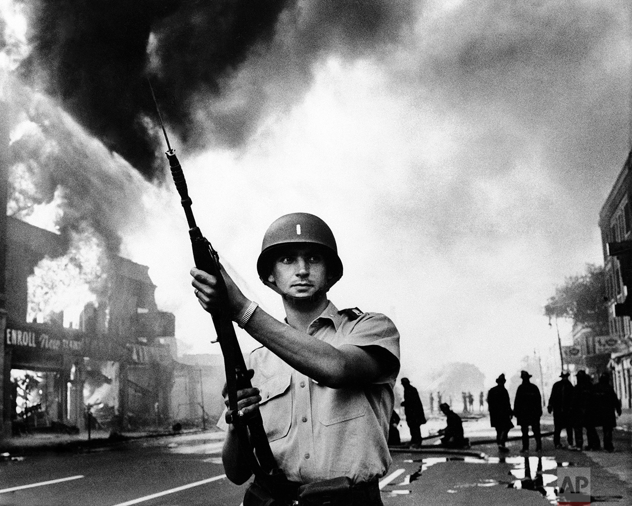 Michigan national guardsmen stood at the ready as firemen battled one of the numerous blazes in riot-torn district of Detroit in July 1967. Riots ripped the motor city following similar demonstrations in New Jersey. (AP Photo)