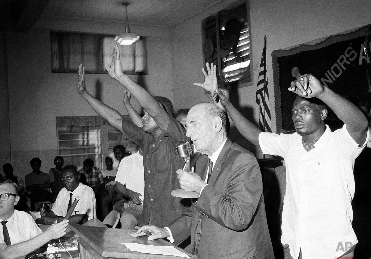 Black leaders hold up their hands for quiet at a meeting with Tampa city officials so Mayor Nick Nuccio can be heard in Tampa, Florida, June 13, 1967. Officials and black residents met in the riot area of the city to air their grievances and to head off further racial trouble. (AP Photo/Jack Thornell)