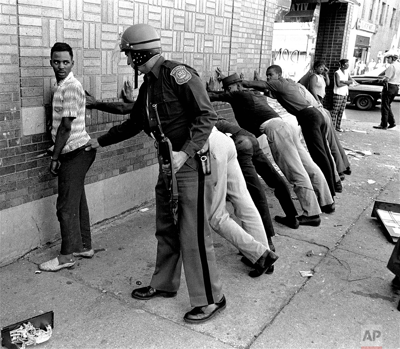 A Michigan State officer searches a youth on Detroit's 12th Street, July 24, 1967, where looting was still in progress after the city's rioting. His companions lean against the wall waiting their turn. There were many arrests and at least five persons were dead. (AP Photo)