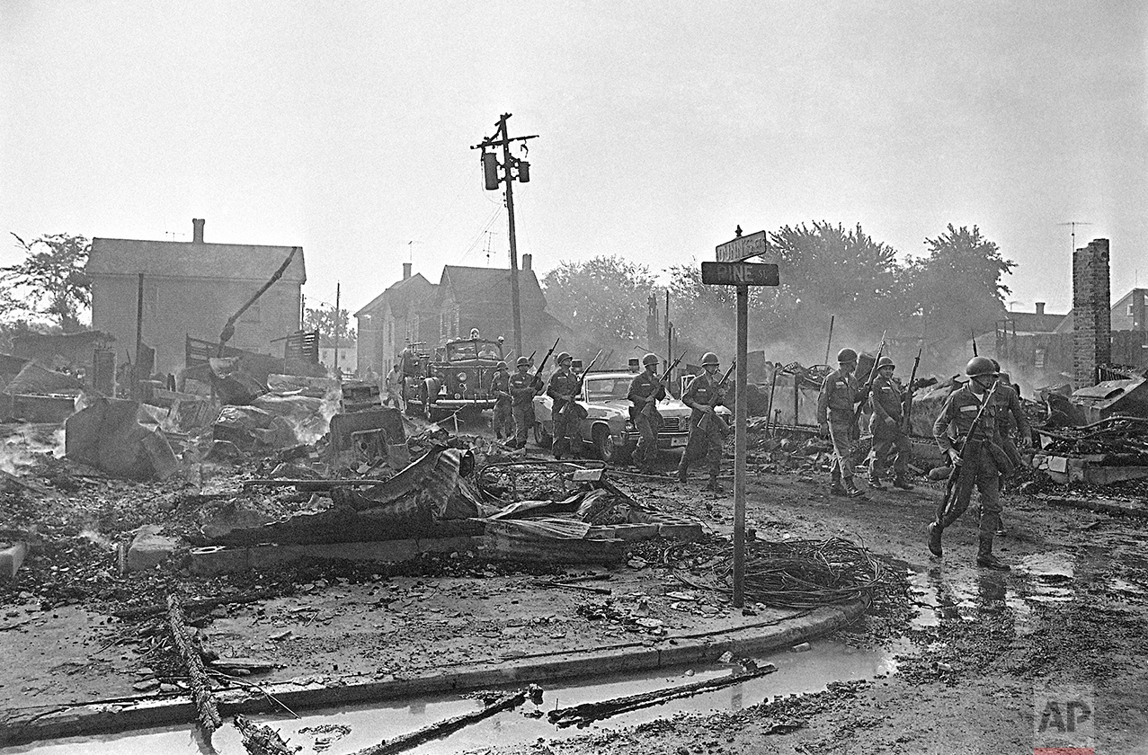 Armed Maryland National Guardsmen precede a fire truck moving into the riot area of Cambridge, Maryland, July 25, 1967 as debris from last night's fires in a leveled block-long area continued to smolder and burn. (AP Photo/Bob Schutz)