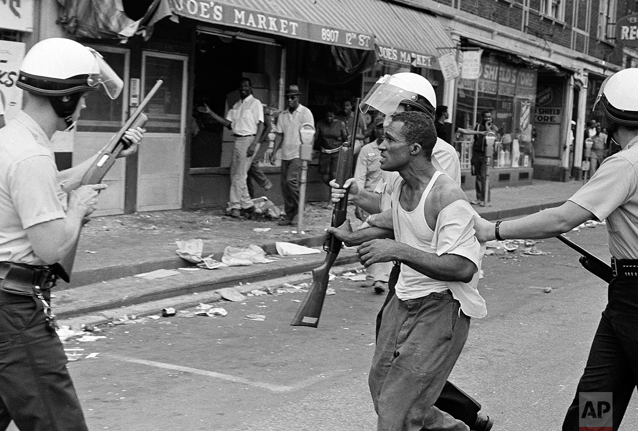 """Congressman John Conyers, Detroit Democrat, uses a bullhorn as he tried to encourage African American in Detroit's riot area to go home, July 23, 1967. He was met with shouts of """"No, no."""" As Conyers stepped down a rock hit the street a few feet from him. (AP Photo)"""
