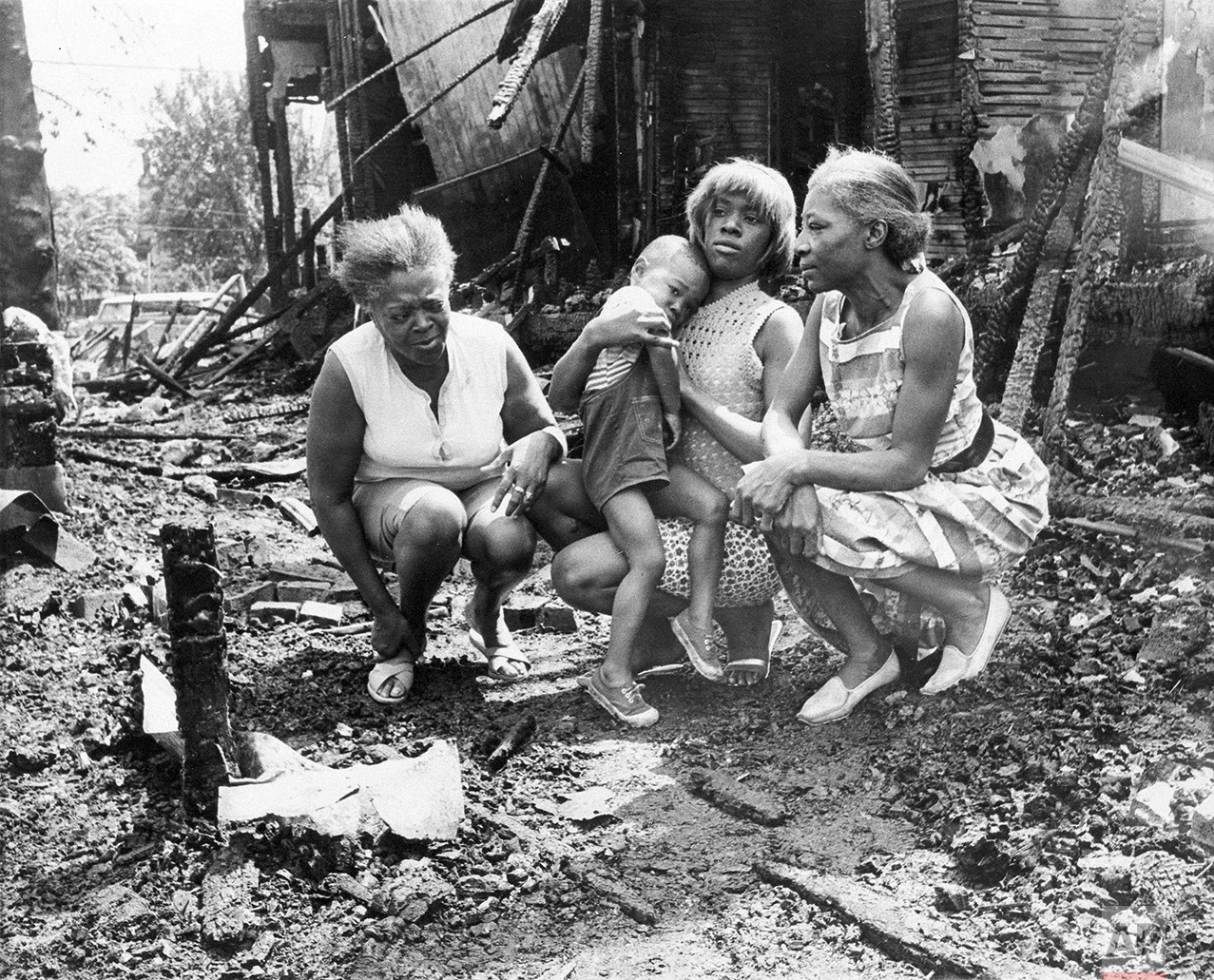 Three women and a child visit the charred ruins of what used to be their home in the 12th Steet area of Detroit, Mich., July 26, 1967. Homes were burned out by fire bombs thrown by rioters. The women are typical of many innocent people who lost all of their possessions in the fires. from Left are: Mrs. Willie Moore; Mrs. Elizabeth Allen, holding son, Thomas, 3; and Mrs. Louella Underwood. (AP Photo/Detroit News)
