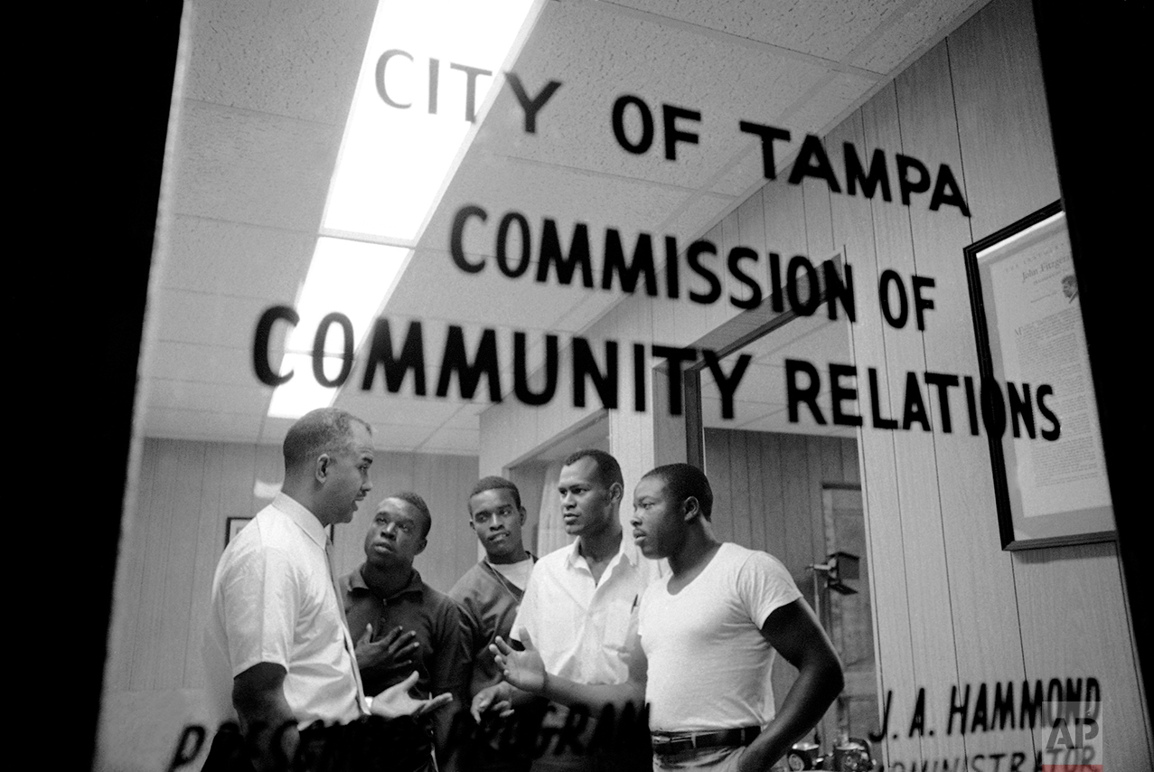 J.A. Hammond, left, administrator of community relations for the City of Tampa, Florida, met with the four platoon leaders of the newly formed Youth Patrol which helped to restore order to the riot torn sections of Tampa, June 15, 1967. From left are Hammond, Robert Dixon, Arthur Lee Roby, Carl Brazelton, and Johnnie Lee Carter. They decided to ask the city to make the Youth Patrol a permanent organization. (AP Photo/Toby Massey)