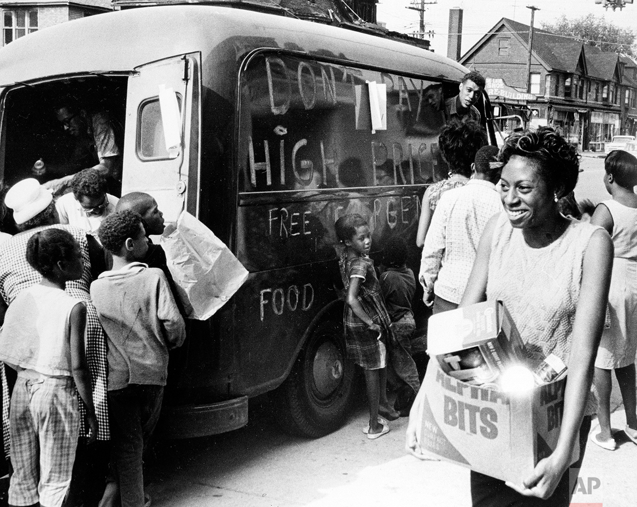 """People gather around a truck to get free food on Detroit's east side, July 27, 1967. The food was brought to the riot-stricken area by the Crisis Council, one of the many organizations aiding residents. Sign on the side of the truck reads """"Don't pay high prices - free emergency food.""""(AP Photo)"""
