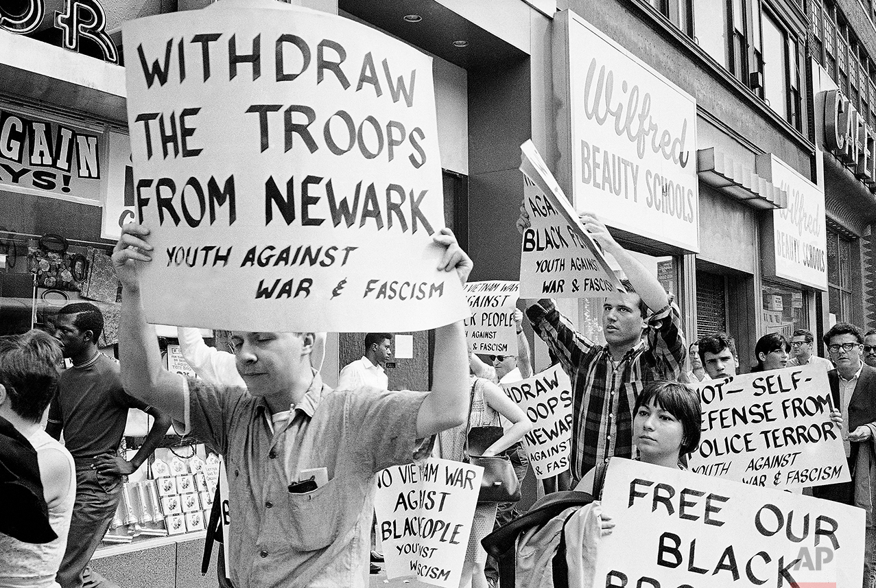 Pickets calling for the removal of National Guard troops from riot-ridden Newark march near Newark City Hall, July 16, 1967. Police arrived shortly after they began marching and dispersed the group. Marchers handed out handbills calling action against rioters full scale war. (AP Photo)