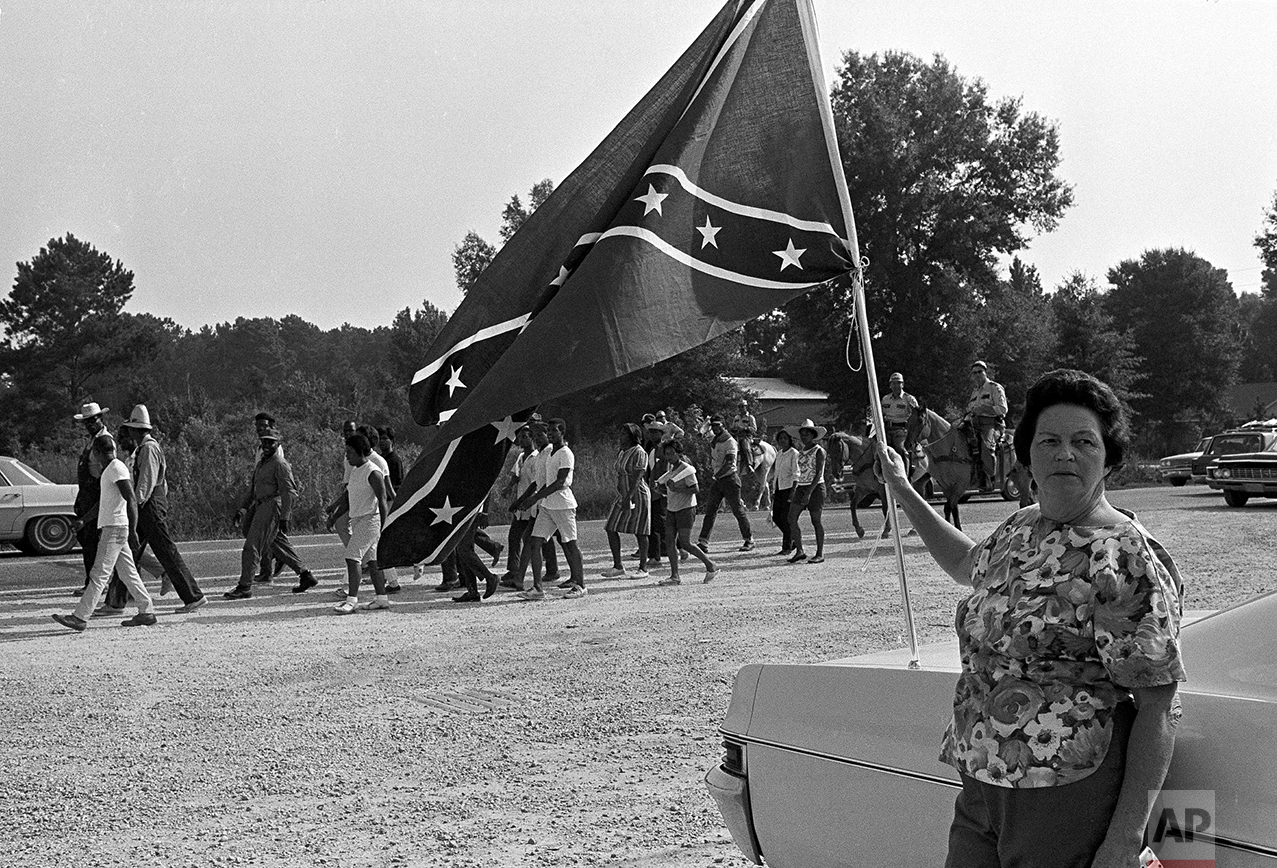 A white woman stands in protest by a confederate flag fluttering in the breeze as a group of 20 civil rights marchers pass through Hammond, La., Aug. 14, 1967. Racial shooting erupted last night in Hammond leaving five white men wounded. Twelve African-Americans were arrested in the shooting. The marchers, who camped at Hammond last night, are en route to Baton Rouge, La., to present a list of demands to the governor. (AP Photo/Jack Thornell)