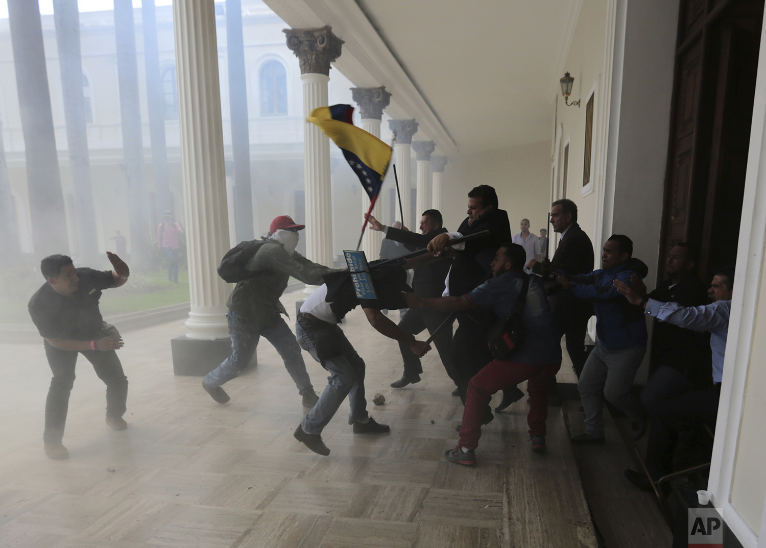 Opposition lawmakers fight with pro-government militia members who are trying to force their way into the National Assembly during a special session coinciding with Venezuela's independence day, in Caracas, Wednesday, July 5, 2017.  (AP Photos/Fernando Llano)