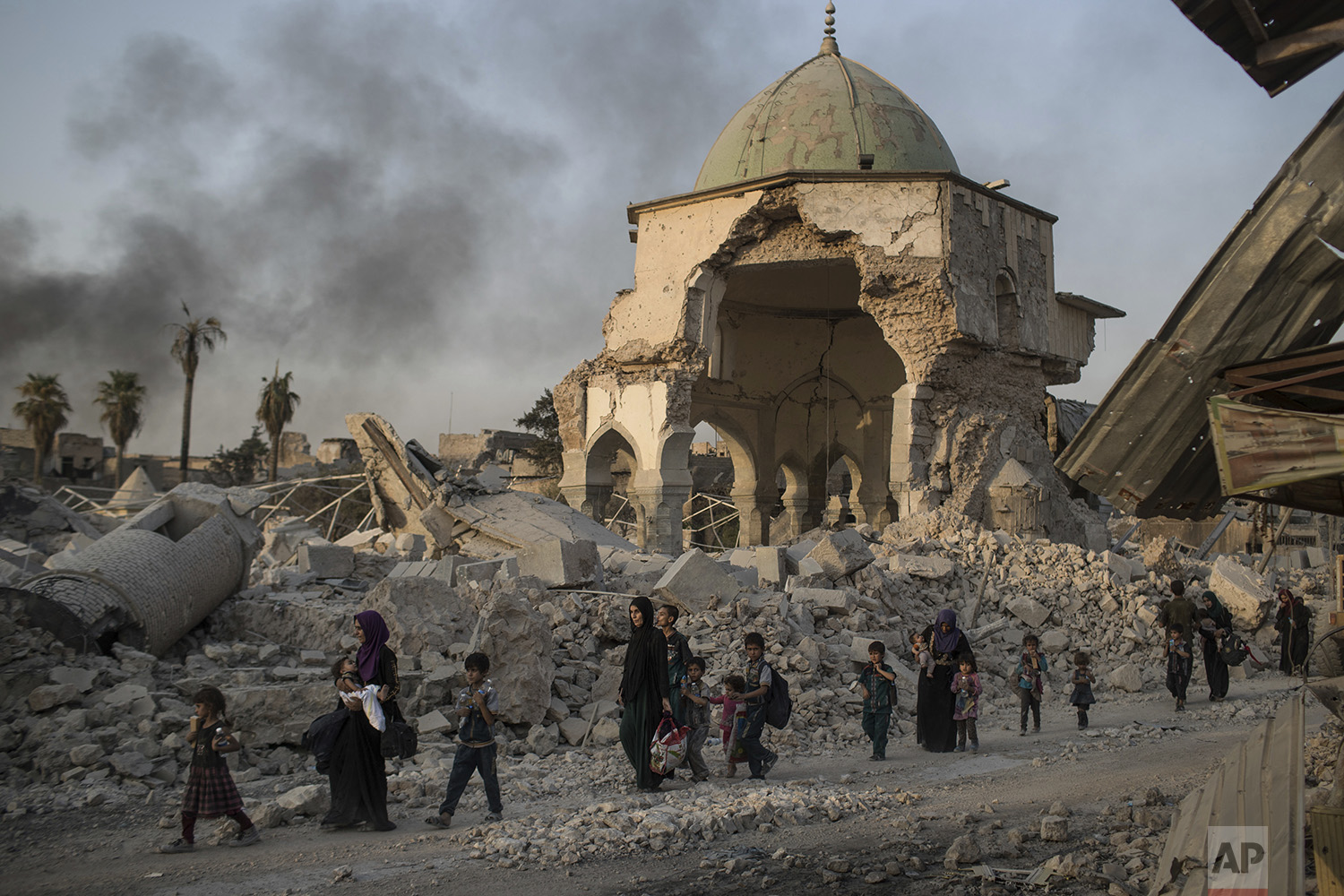 Fleeing Iraqi civilians walk past the heavily damaged al-Nuri mosque as Iraqi forces continue their advance against Islamic State militants in the Old City of Mosul, Iraq, Tuesday, July 4, 2017. (AP Photo/Felipe Dana)