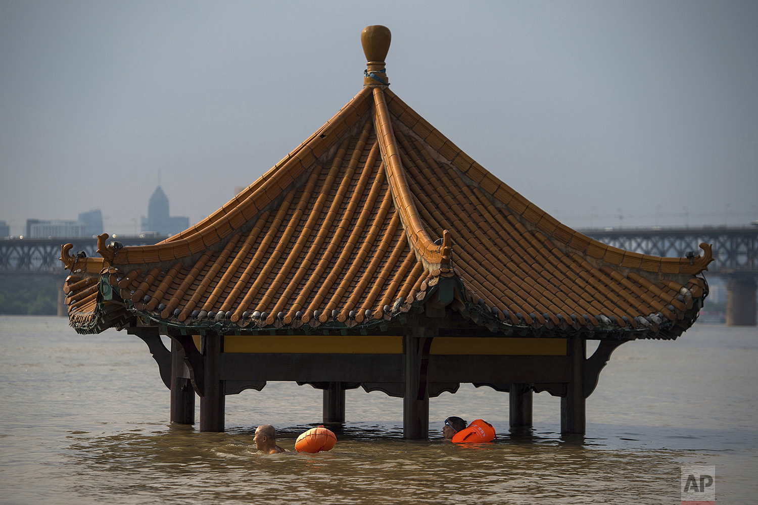 People swim past the top of a pagoda at a flooded riverside park in Wuhan in central China's Hubei Province on Monday, July 3, 2017. (Chinatopix via AP)