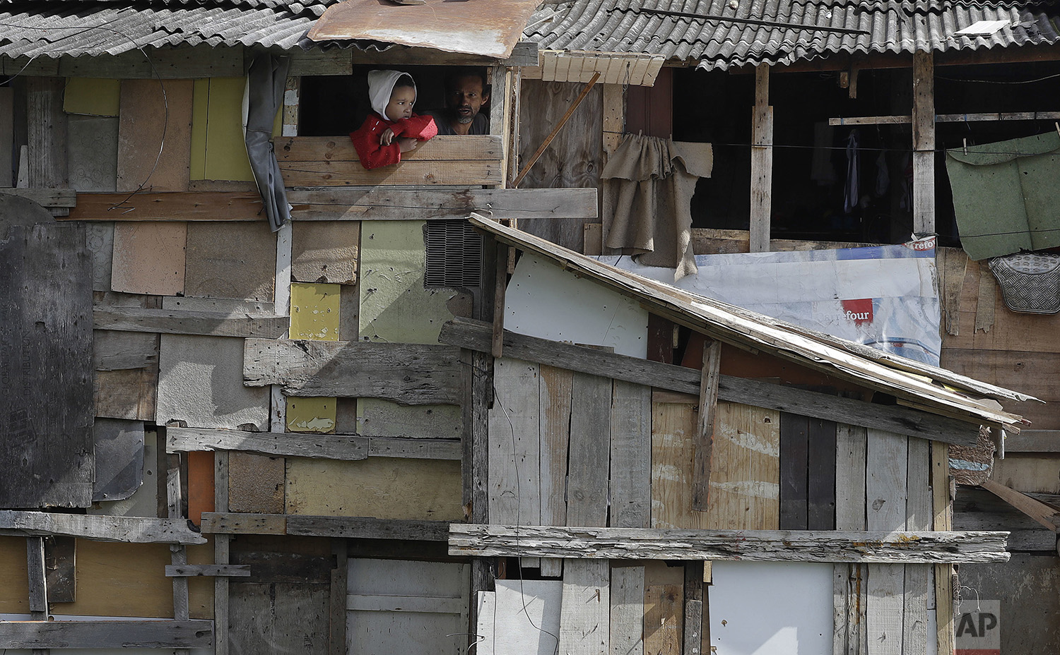A boy peers from his home's window as firefighters extinguish the last flames of a nearby fire in the Osasco neighborhood of the greater Sao Paulo area of Brazil, Monday, July 3, 2017. (AP Photo/Andre Penner)