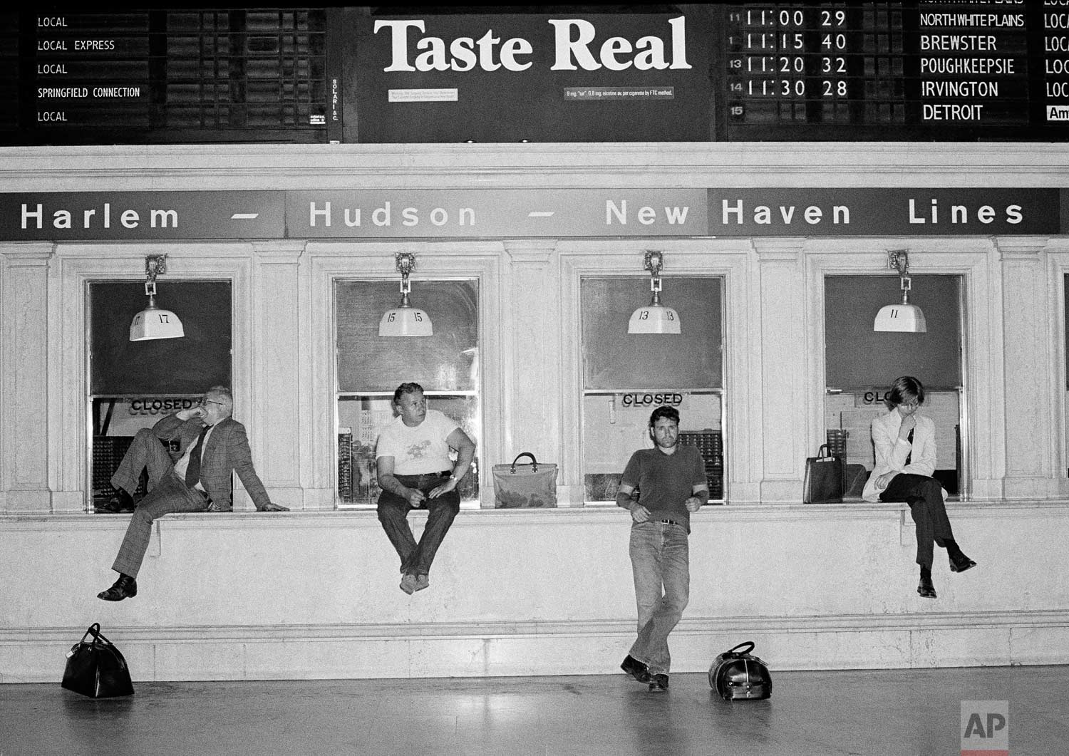Commuters wait at empty ticket windows at Grand Central Station in New York City, early on July 14, 1977, as trains were canceled by the electric power failure that affected most public transportation in the city. (AP Photo/Carlos Rene Perez)