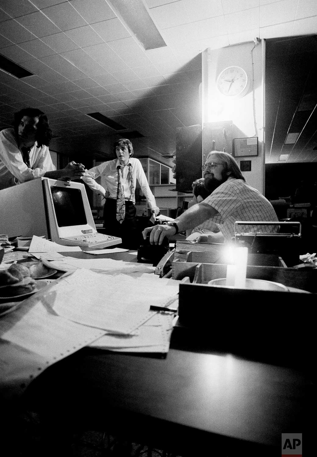 Using emergency power, staffers on the Associated Press general desk plan coverage of the blackout in New York City, July 13, 1977, in New York. Clock at upper right shows time power went out at AP. (AP Photo/Cameron Bloch)