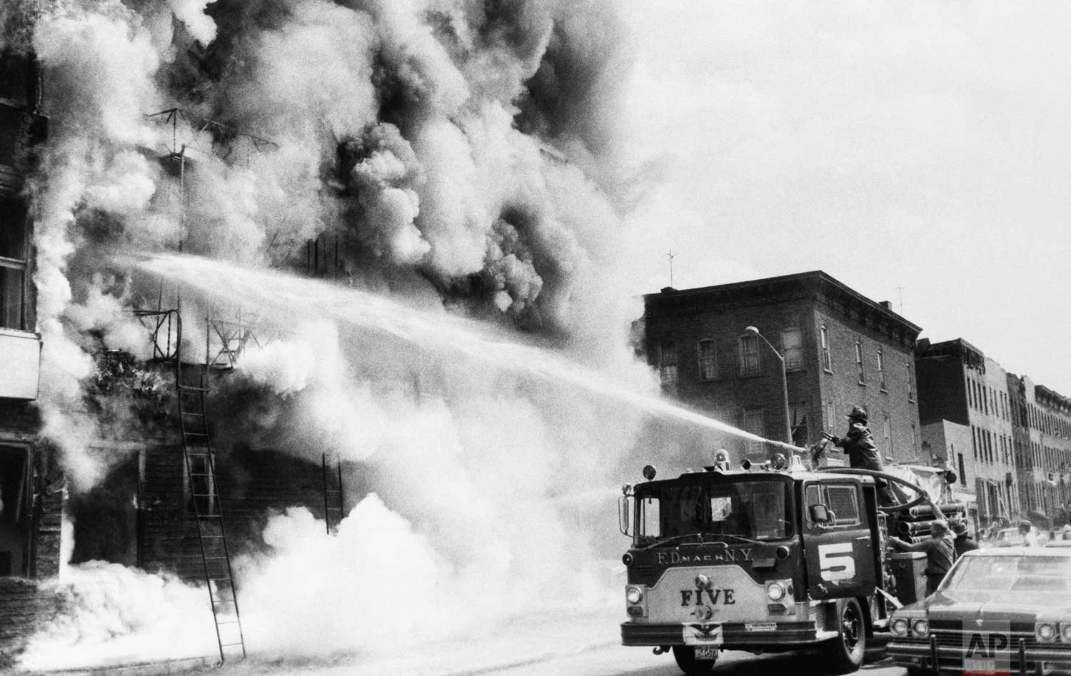 Firemen fight a blaze above a row of looted stores in New York's Brooklyn borough, July 14, 1977, the day after the power failure. The stores were looted during blackout. (AP Photo)