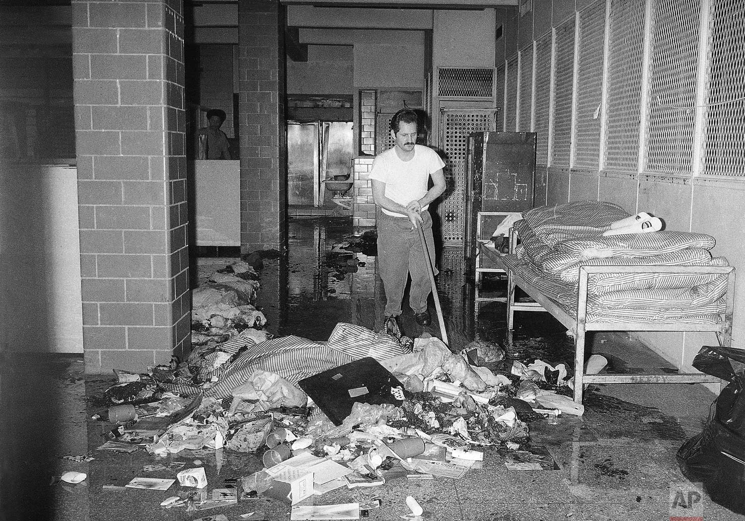 An inmate cleans up mess at the Bronx House of Detention in New York on Thursday, July 14, 1977. Corrections officials said inmates caused damage in three dormitories during the electric power failure that struck New York on Wednesday, July 13. (AP Photo/Marty Lederhandler)