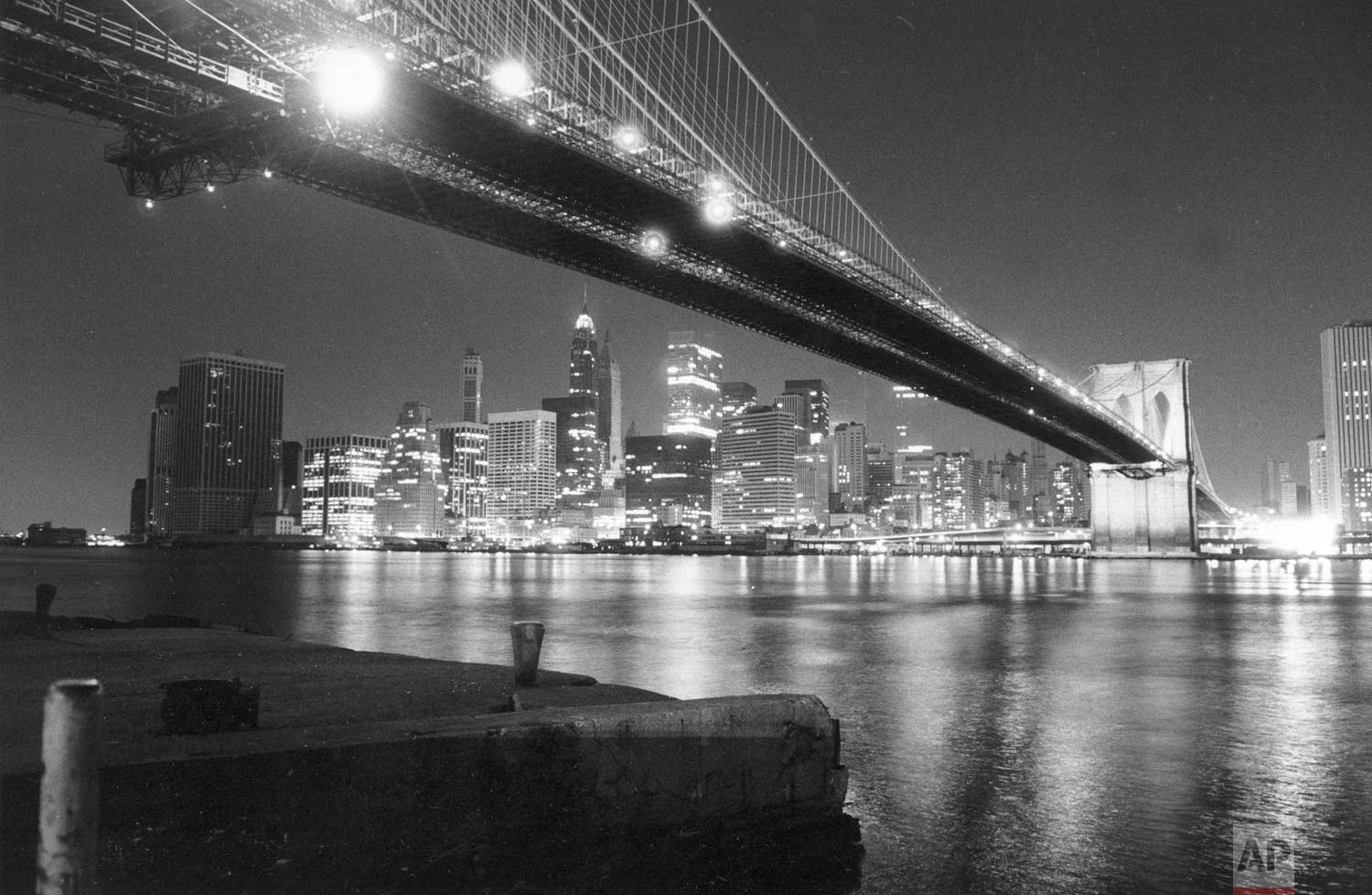 The lights of lower Manhattan shine across New York's East River in this nighttime view from under the Brooklyn Bridge on July 14, 1977.  Power has been restored in about 90 percent of the city, 24 hours after a city-wide electrical blackout.  (AP Photo/Ray Stubblebine)