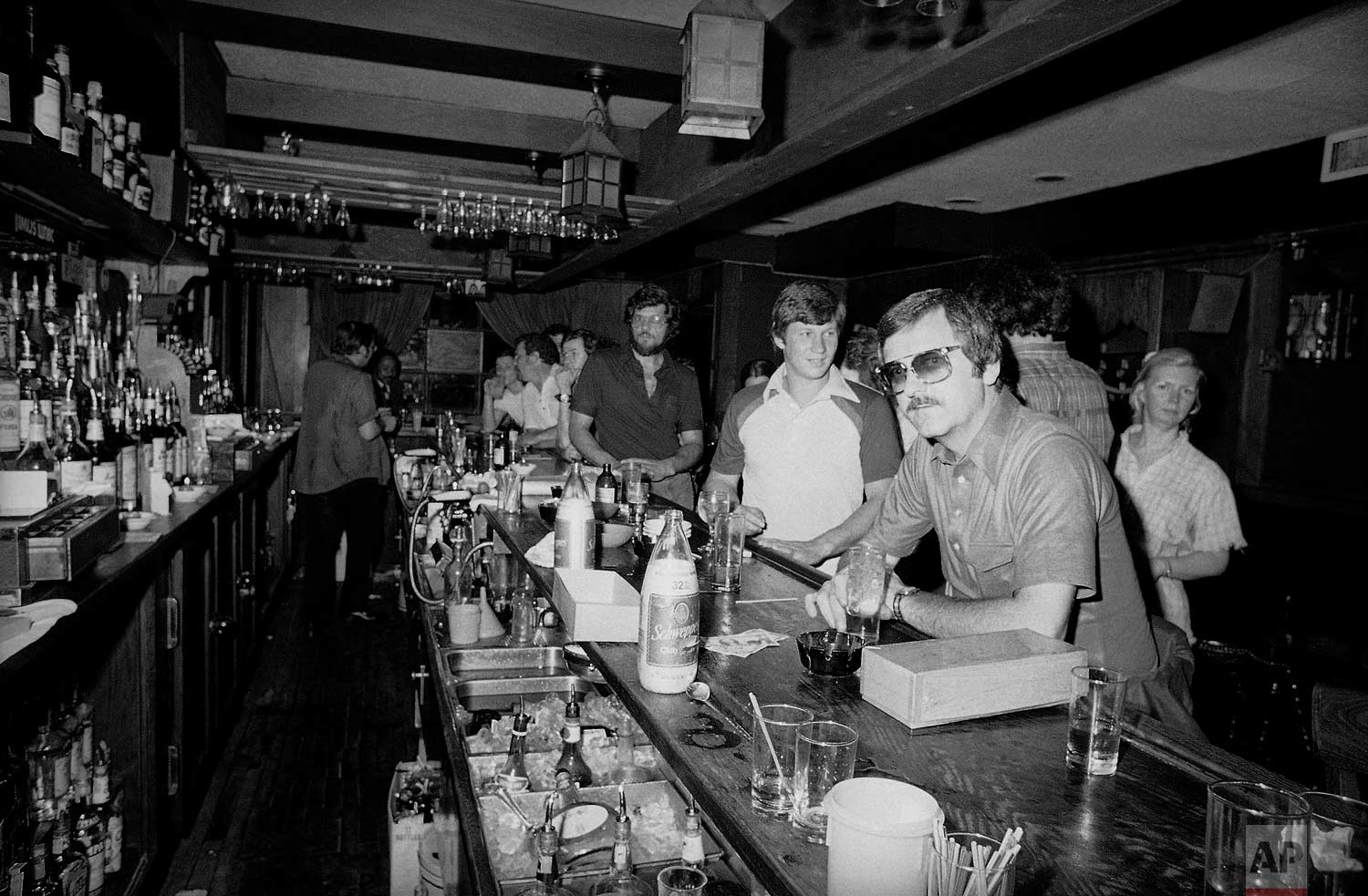 People in a midtown Manhattan bar keep drinking by candlelight in New York on Wednesday, July 13, 1977 after the city was struck by a power failure. (AP Photo/Steve Oualline)