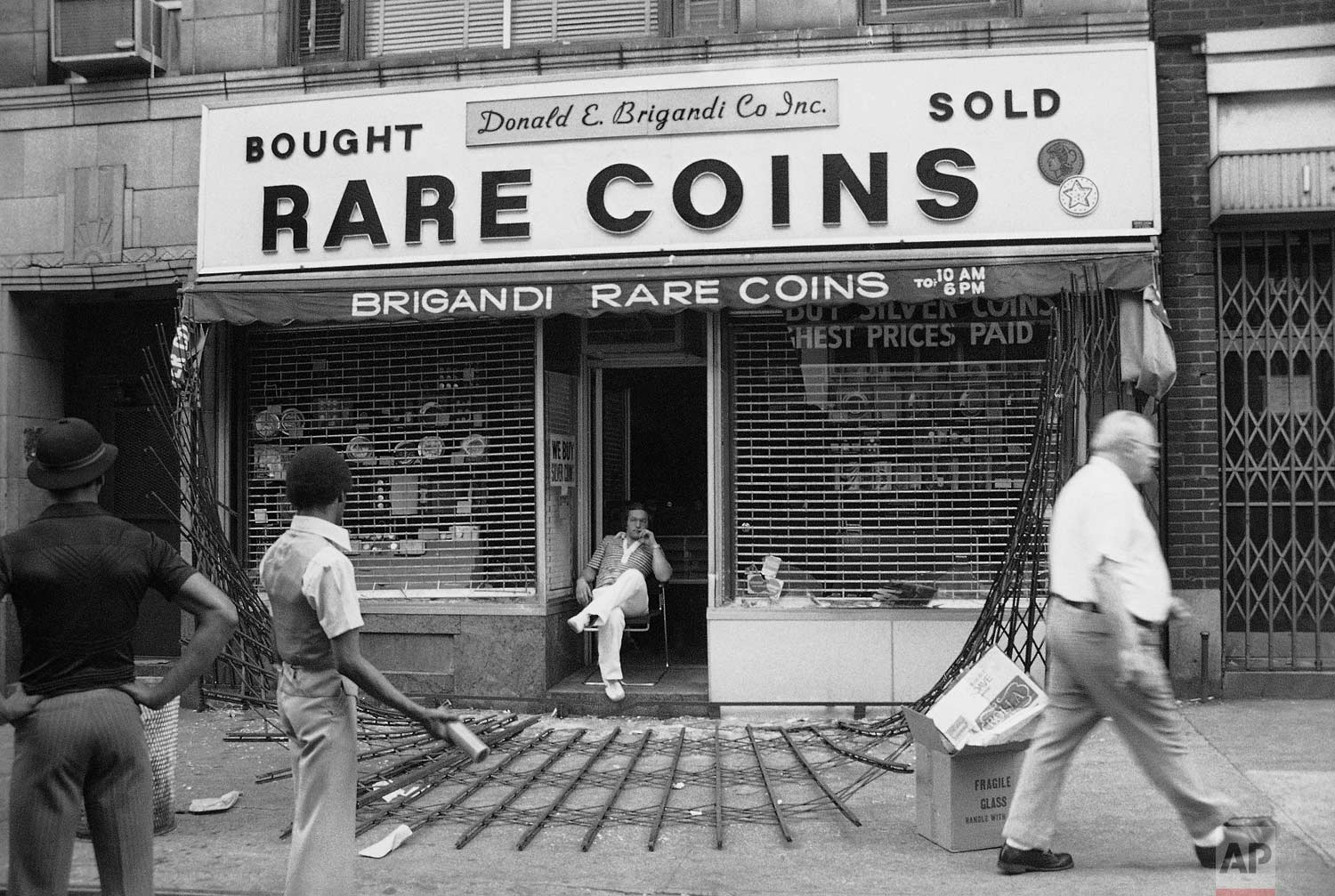 """The owner of midtown Manhattan coin shop sits disconsolately in his doorway in New York on Thursday, July 14, 1977. The steel gates protecting the shop were ripped down by looters. """"They sure cleaned me out,"""" he said. (AP Photo/Sandy Colton)"""