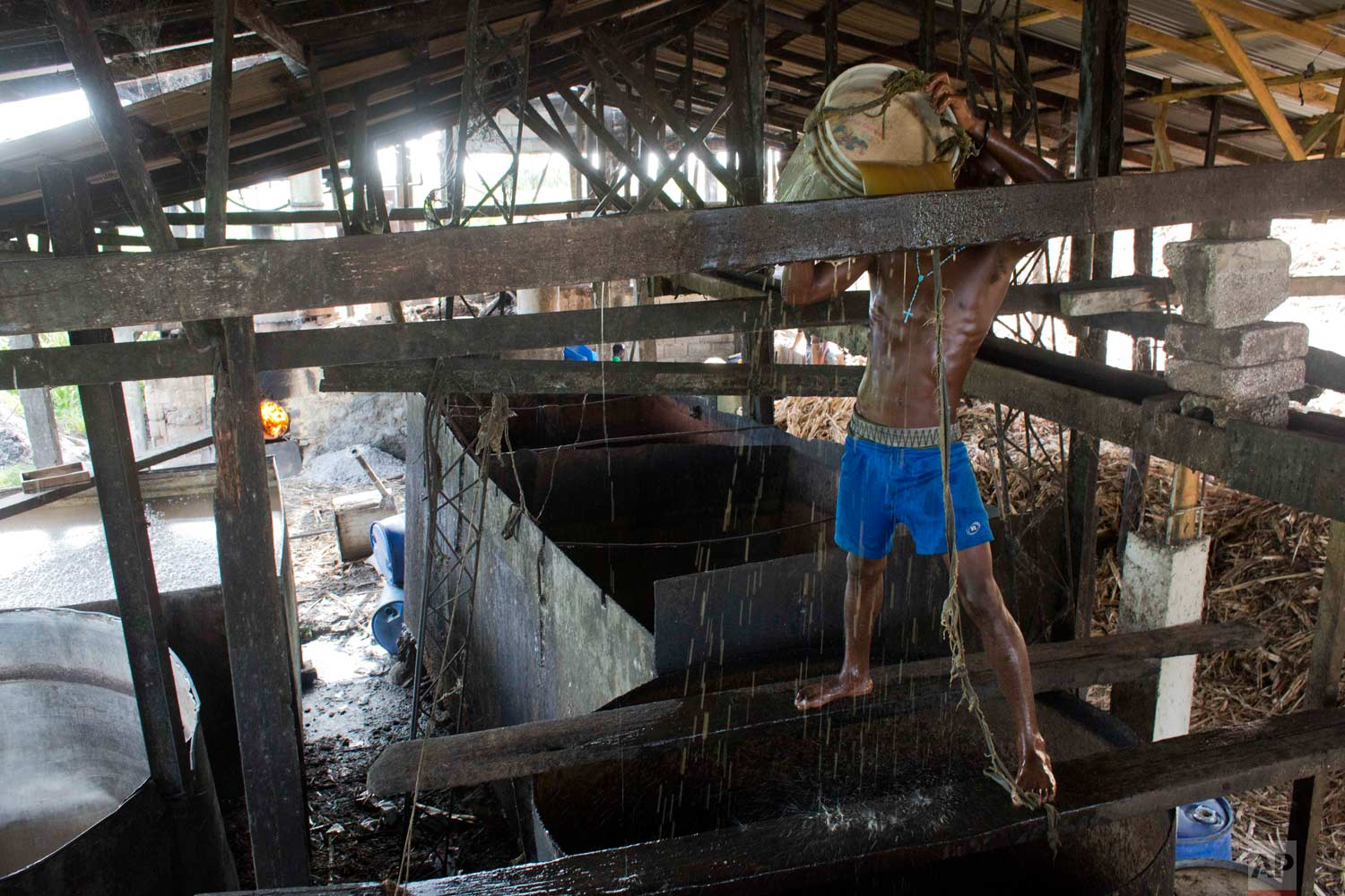 In this June 19, 2017 photo, Gabriel Shnaider, 22, pours sugar cane water into a boiler at the Ti Jean distillery, which produces clairin, a sugar-based alcoholic drink, in Leogane, Haiti. At Ti Jean, after the juice is fermented and filtered, it is shipped in plastic jugs to be sold in market stalls and by street merchants around the region. Individual retailers add flavors with herbs or fruit. (AP Photo/Dieu Nalio Chery)