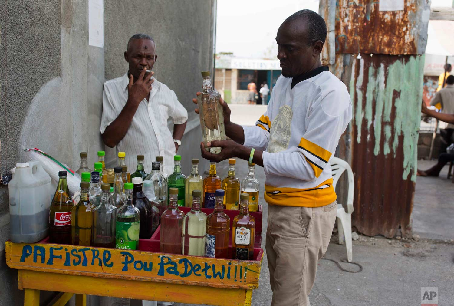 Eddy Lecty shakes a bottle of clairin, a sugar-based alcoholic drink, after adding clove spice to it, as his father Wilfrid Yves Nader smokes nearby and they wait for customers in the Cite Soleil area in Port-au-Prince, Haiti, Tuesday, July 11, 2017. The father-son business has been selling different flavors of clairin at this spot for almost 20 years, which has turned into a meeting place locals coined The Citizens Club. (AP Photo/Dieu Nalio Chery)