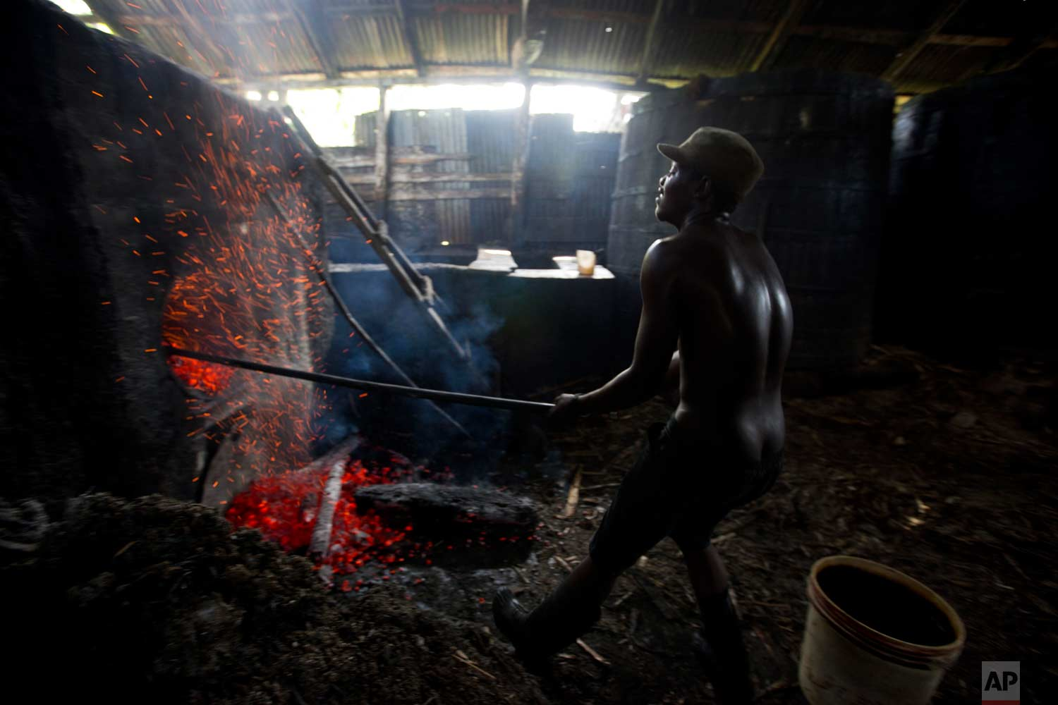 In this June 16, 2017 photo, Batel Delciner, 23, removes wood from a furnace to lower the heat cooking sugar juice at the Ti Jean distillery, which produces clairin, a sugar-based alcoholic drink, in Leogane, Haiti. The broth is cooked for about four hours after a fermentation period of four to eight days. (AP Photo/Dieu Nalio Chery)