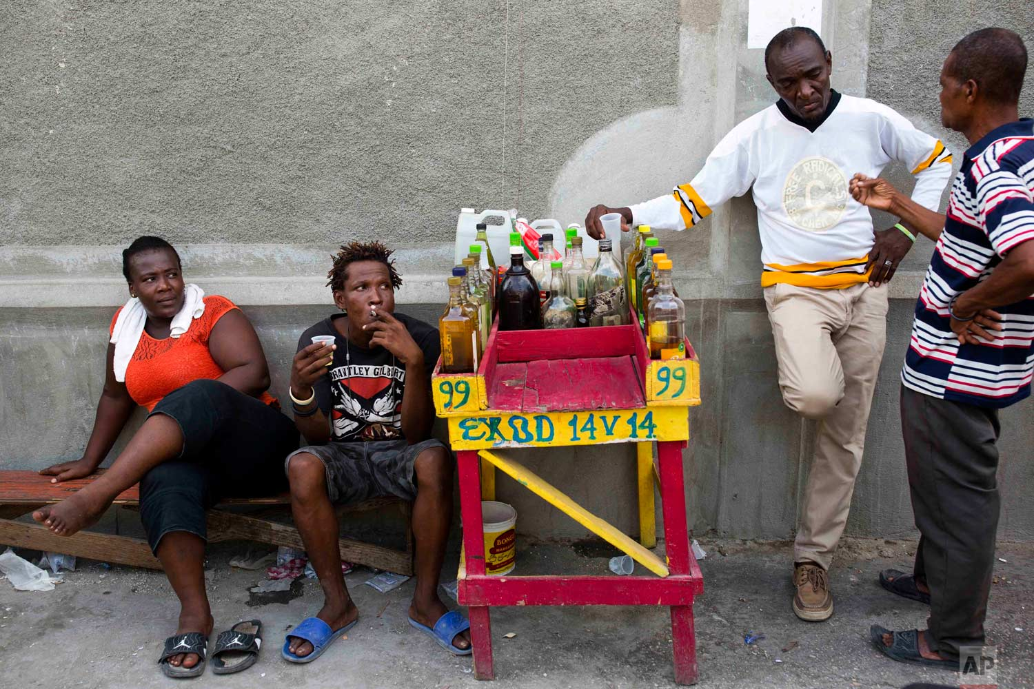Eddy Lecty, who sells the sugar-based alcoholic drink known as clairin, second from right, talks to a client as his relative Junior Lecty and local Suzie Bazil, left, sit nearby in the Cite Soleil area of Port-au-Prince, Haiti, Tuesday, July 11, 2017. Eddy Lecty, who's selling spot has been coined by locals The Citizens Club, says people trust his product and former Haitians presidents like Rene Preval and Michel Martelly have stopped by to have a drink. (AP Photo/Dieu Nalio Chery)