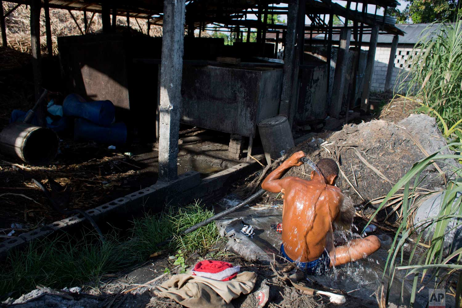 In this June 19, 2017 photo, a man washes off at the end of his eight-hour shift carrying bagasse, the fiber left over after pressing juice from sugar cane, at the Ti Jean distillery, which produces clairin, a sugar-based alcoholic drink, in Leogane, Haiti. Clairin, or kleren as it's known in Haitian Creole, is produced at hundreds of small distilleries scattered throughout Haiti. (AP Photo/Dieu Nalio Chery)