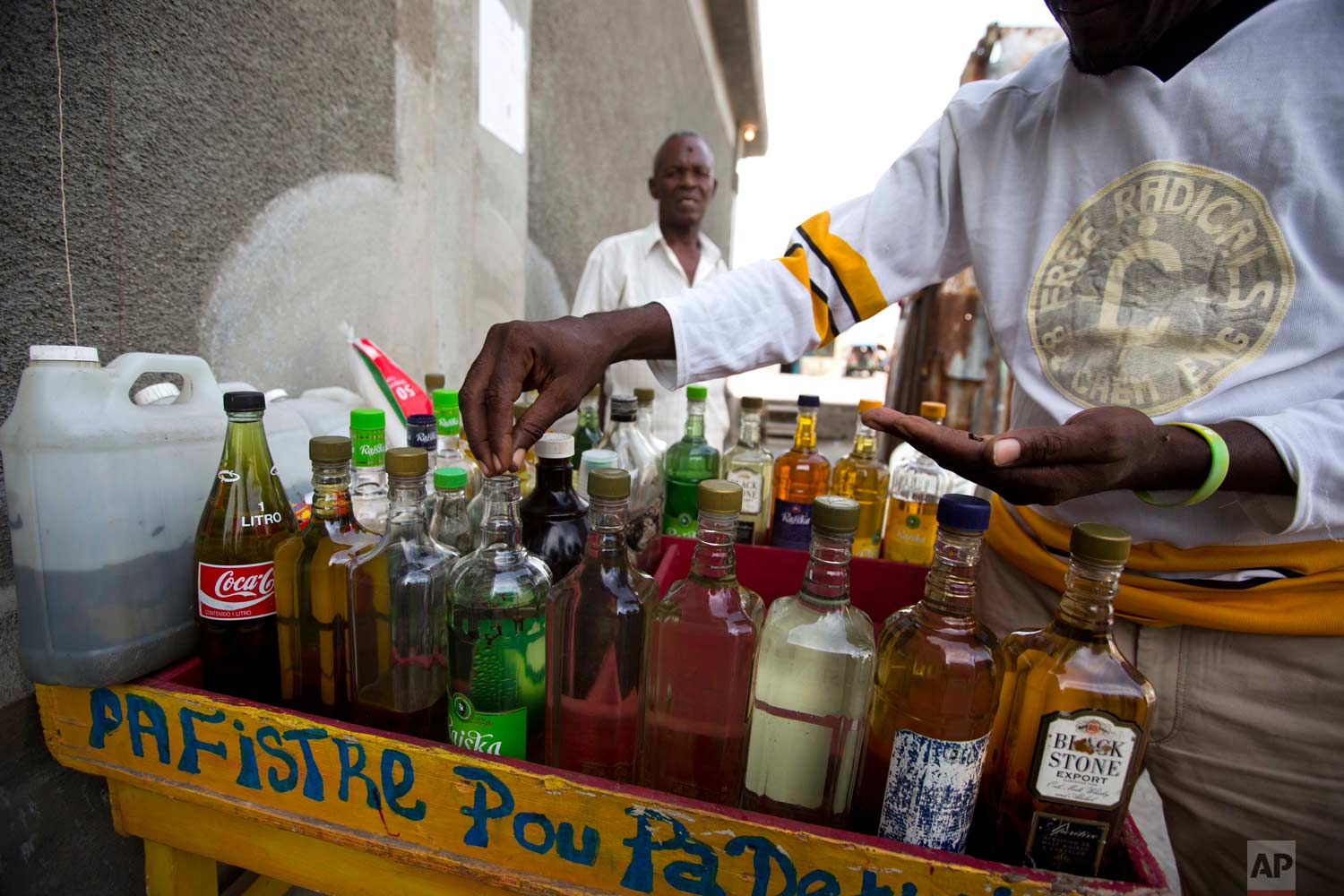 Eddy Lecty, who sells a sugar-based alcoholic drink known as clairin, adds cloves to spice up one of his bottles in the Cite Soleil area of Port-au-Prince, Haiti, Tuesday, July 11, 2017. Individual retailers who add flavors with herbs or fruit to the less refined version of rum reuse bottles carrying other labels. (AP Photo/Dieu Nalio Chery)
