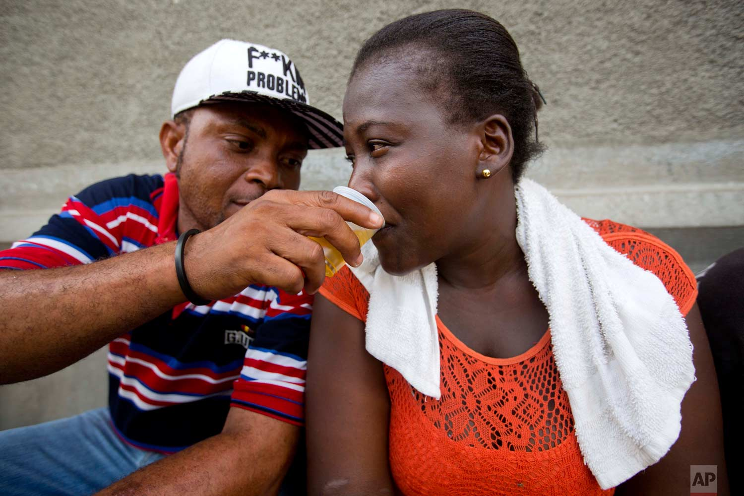 A man shares his clairin as he sits on the sidewalk where a vendor sells the sugar-based alcoholic drink in the Cite Soleil area of Port-au-Prince, Haiti, Tuesday, July 11, 2017. Clairin is rum's rustic cousin, a drink that's much cheaper and relatively rare outside this struggling Caribbean country. (AP Photo/Dieu Nalio Chery)