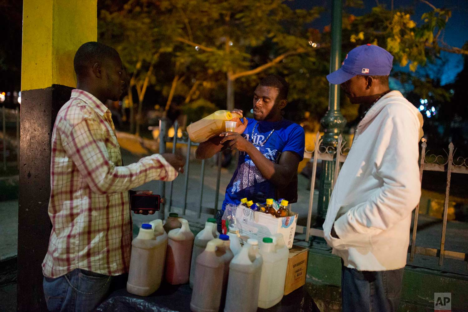 In this June 23, 2017 photo, Smith Nazon, 29, sells clairin, a sugar-based alcoholic drink, on the sidewalk in Petion-Ville, Haiti. A 1 liter bottle sells for about $1.36 dollars, about one-eighth the price of the least expensive bottle of Barbancourt rum, Haiti's most famous export. (AP Photo/Dieu Nalio Chery)