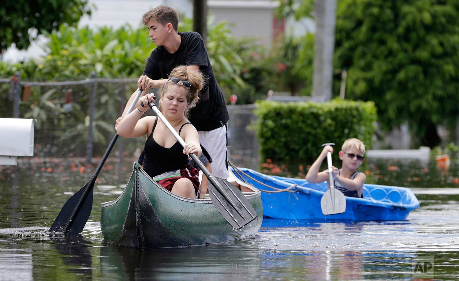 """Isabella and Timothy, who did not want their last names used, navigate flooded streets following heavy rains, Wednesday, June 7, 2017, in Davie, Fla. Several South Florida cities set rainfall records as heavy rain continues to fall, bringing the potential for further flooding. Wallace put up the """"Slow No Wake"""" sign to prevent fast moving vehicles from flooding her trailer. (AP Photo/Lynne Sladky)"""